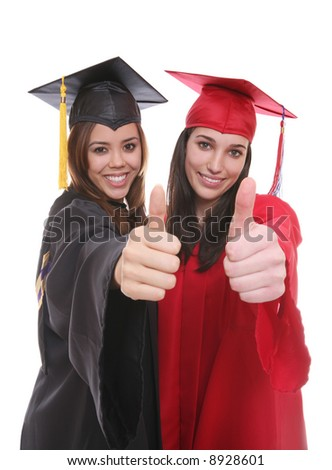 Two pretty women friends with thumbs up at graduation - stock photo
