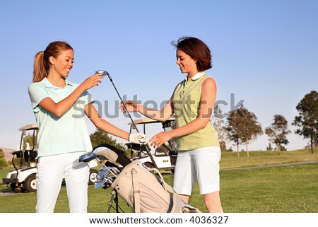 Two pretty women golfers selecting a golf club - stock photo