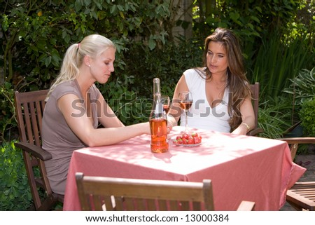 Two pretty women having a conversation in the garden while drinking a glass of wine - stock photo