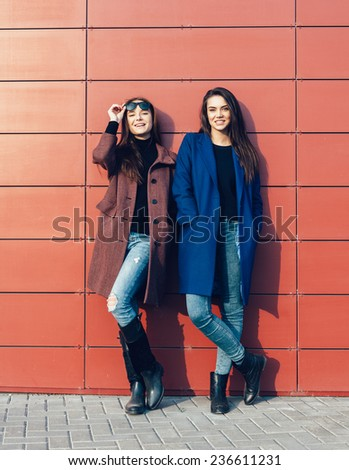 Two pretty women  in a coats posing near red wall on a sunny day. Outdoor lifestyle portrait - stock photo