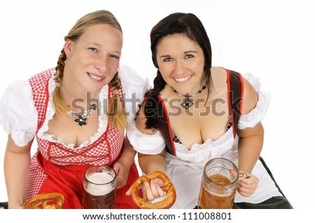 two pretty women in dirndls and pretzels / munich beer festival - stock photo