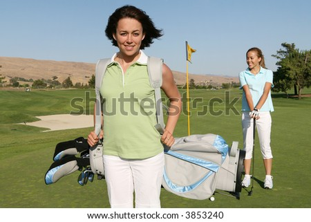 Two pretty women in the middle of a golf game - stock photo