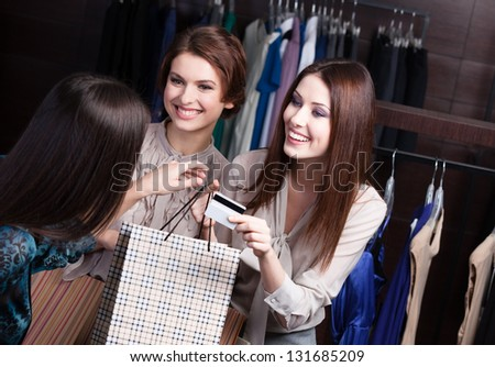 Two pretty women pay with credit card - stock photo