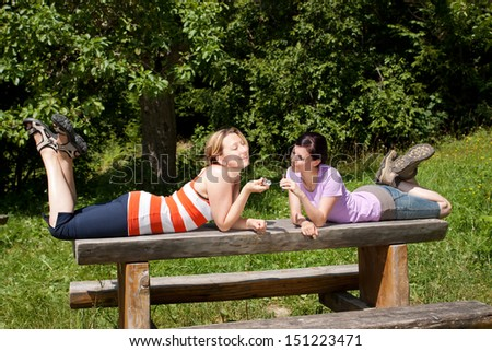 two pretty women relax in nature - stock photo