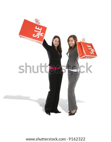 Two pretty women with sale bags looking happy - stock photo