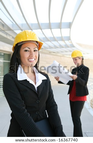 Two pretty women working as  architects on a construction site