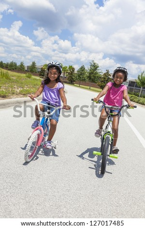 Two pretty young African American girls with a big smiles riding bicycles outside - stock photo