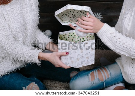 Two pretty young funny girls friends smiling and having fun, holding bright holiday presents, ready for celebration, close view - stock photo