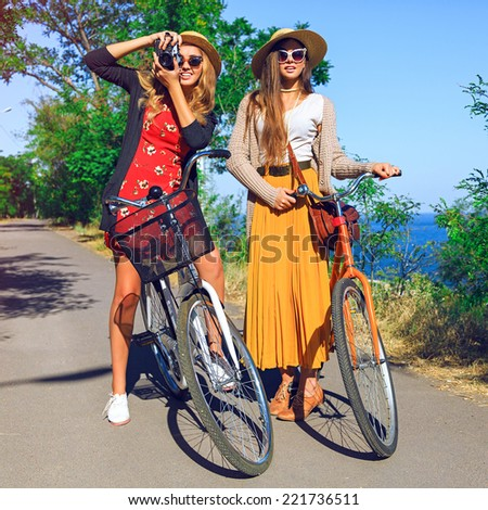 Two pretty young playful girls, walking near sea side with retro bikes, best friends having fun taking pictures of each other, wearing stylish vintage clothes sunglasses and hats. - stock photo