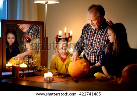 Two pretty young sisters in halloween costumes and their grandpa carving a pumpkin together on Halloween - stock photo