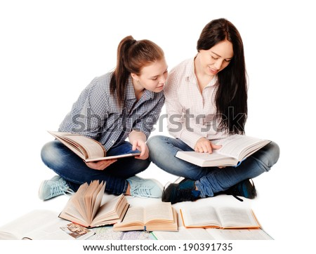 two pretty young student girls studying with books on white background - stock photo