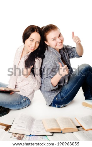 two pretty young student girls studying with books on white background