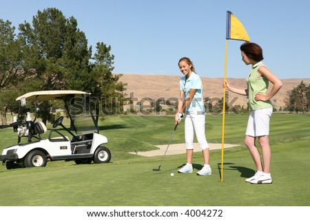 Two pretty young woman golfing on the course - stock photo