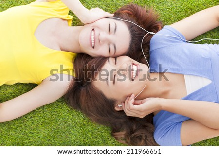 two pretty young woman lying on grassland and listening music  - stock photo
