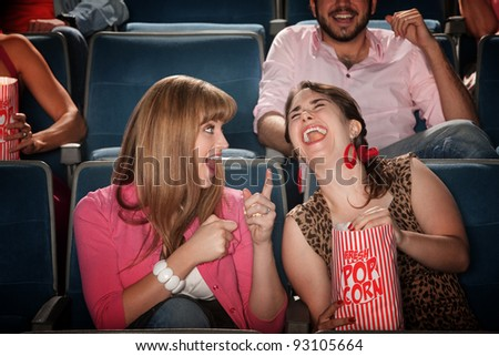 Two pretty young women in the audience laugh together - stock photo