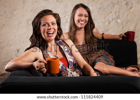 Two pretty young women laughing and holding cups - stock photo