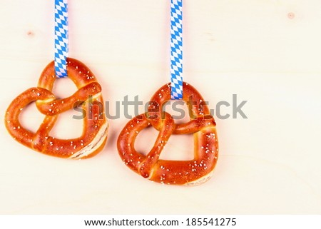Two pretzel in heart shape on wood background, top view - stock photo