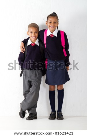 two primary pupils standing against classroom wall - stock photo