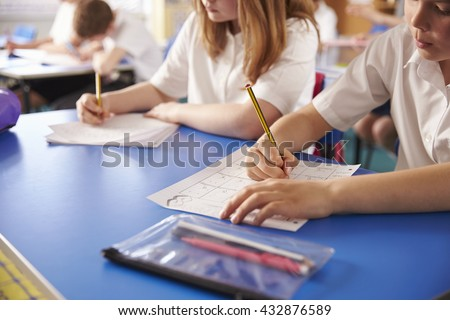 Two primary school kids working in class, close crop - stock photo