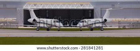 Two private planes in front of a hangar  - stock photo