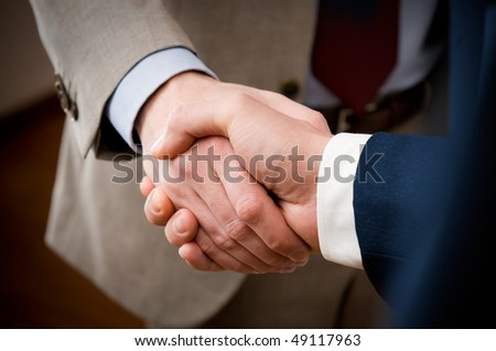 Two professional businessman giving handshake in the office, closeup selective focus - stock photo