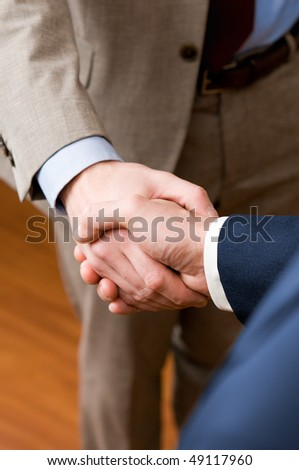 Two professional businessman giving handshake in the office, vertical copy space