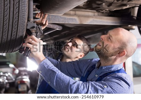 Two professional car mechanics checking up pressure in tires at garage  - stock photo