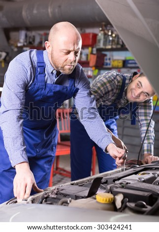 Two professional car mechanics working together at garage  - stock photo