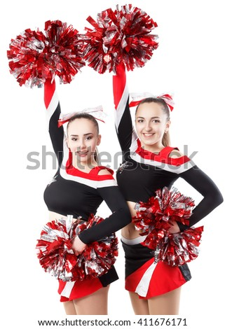 Two professional cheerleaders posing at studio. Hands raised up. Isolated over white. - stock photo