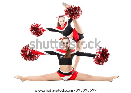 Two professional cheerleaders posing at studio. Side split and vertical split. Isolated over white. - stock photo