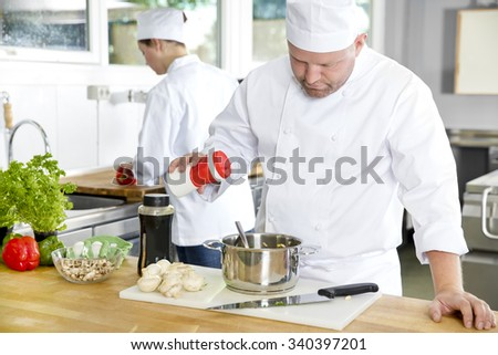 Two professional chefs preparing food in large kitchen - stock photo