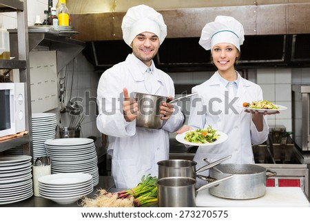 Two professional cookes working at restaurant kitchen  - stock photo