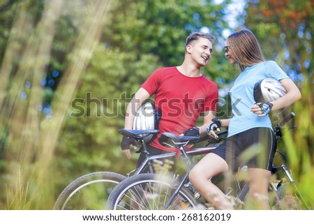 Two Professional Cycling Athletes Standing Together Outdoors with Bikes.Horizontal Image Orientation - stock photo