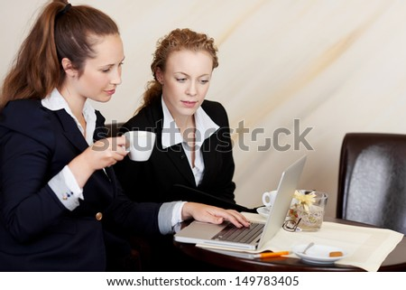 Two professional employees wearing formal clothes while looking at the screen of a laptop, in the office - stock photo