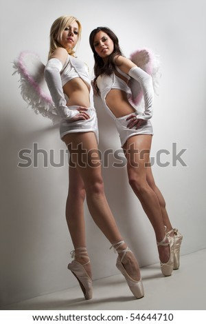 Two professional female ballet dancers with wings  isolated in studio