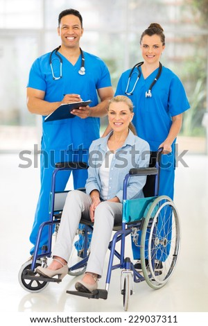 two professional health care workers and disabled patient - stock photo