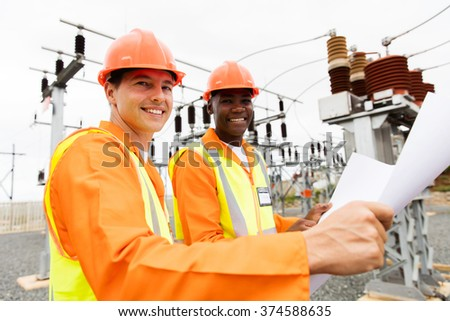 two professional multiracial electricians holding blueprint in substation - stock photo