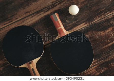 Two professional ping pong rockets lying on vintage wooden table. Black antispin pads. One attack plus, other defense, japan and german made. White ball is near. - stock photo