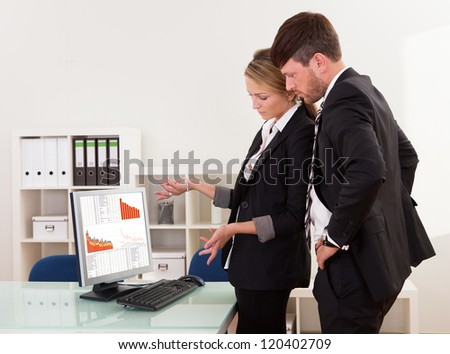 Two professional young business colleagues stand in an office looking at a computer with dropping descending graphs - stock photo