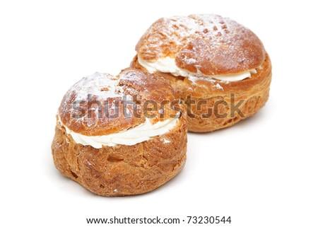 Two profiteroles isolated on white background - stock photo