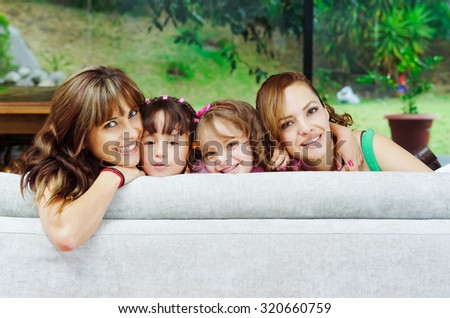 Two proud hispanic mothers posing with their daughters, heads sticking up from sofa and smiling to camera.