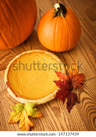 Two pumpkins, a pie and a red leaf on a wooden table.