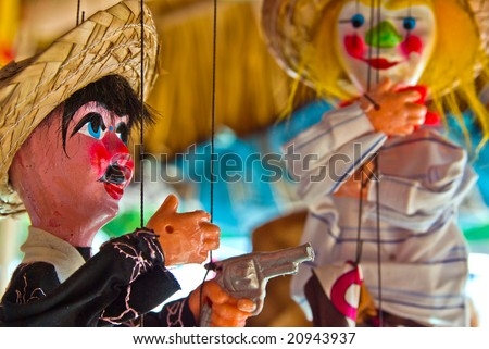 two puppets one holding a gun - stock photo