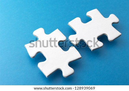 Two puzzle pieces.Close-up of puzzle pieces on blue background. - stock photo