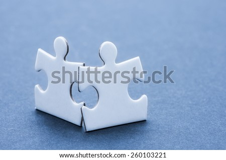Two puzzle pieces. Conceptual image of connection, teamwork and business strategy. - stock photo