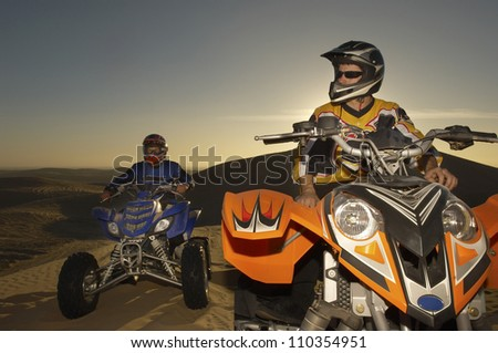 Two quad bike racers sitting on their bike