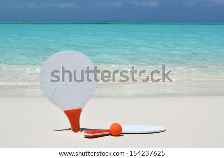 Two rackets and a ball on the sandy beach  - stock photo