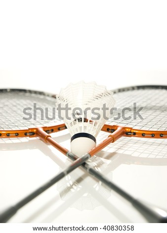 Two rackets crossed and White shuttlecock of badminton - stock photo