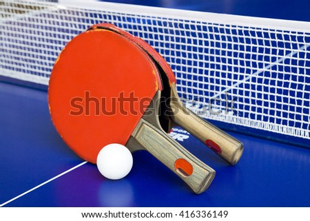 Two rackets for playing table tennis on a blue table.