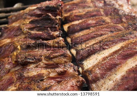 Two racks of grilled ribs are grilling on charcoal - stock photo